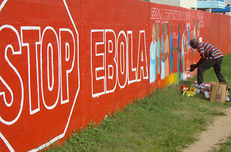 A work of art for educating about Ebola virus disease emerges on the wall at a sports field in Monrovia, paid for by the Liberian Ministry of Health and Social Welfare. Source: Esther Hamblion/WHO