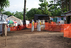 The Doctors Without Borders treatment centre in Guéckédou, Guinea. On the left, patients are sitting under an umbrella. Clothing of doctors and nurses are drying on the right side. Source: Andreas Kurth/RKI